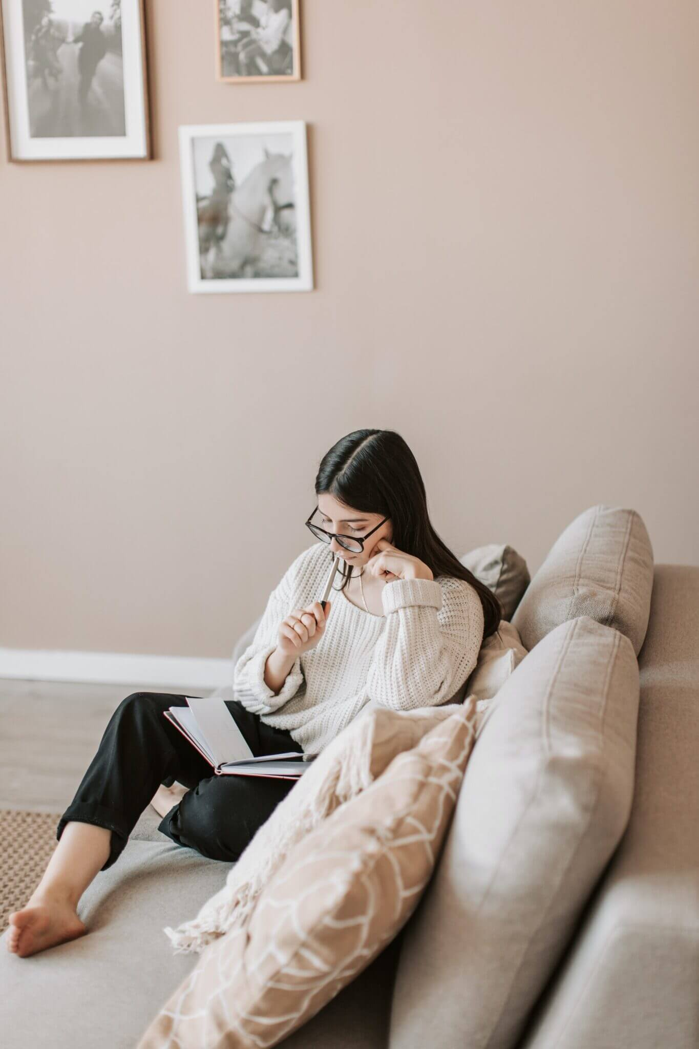 girl journaling on a white sofa