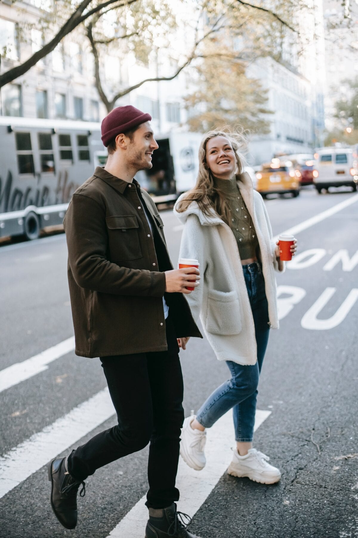 Couple walking on street with coffee cups