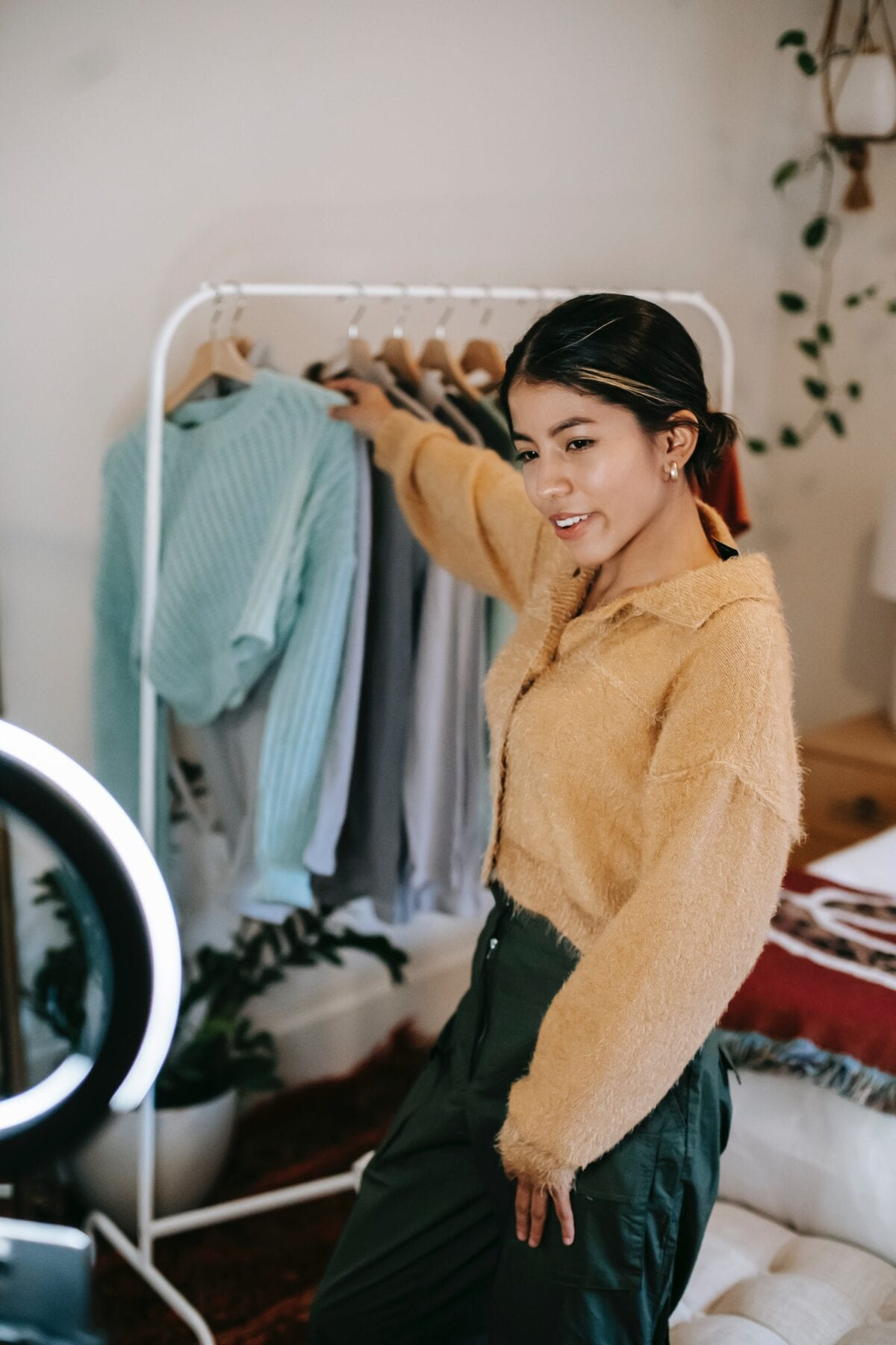 Trendy smiling woman taking clothes from rail while shooting video