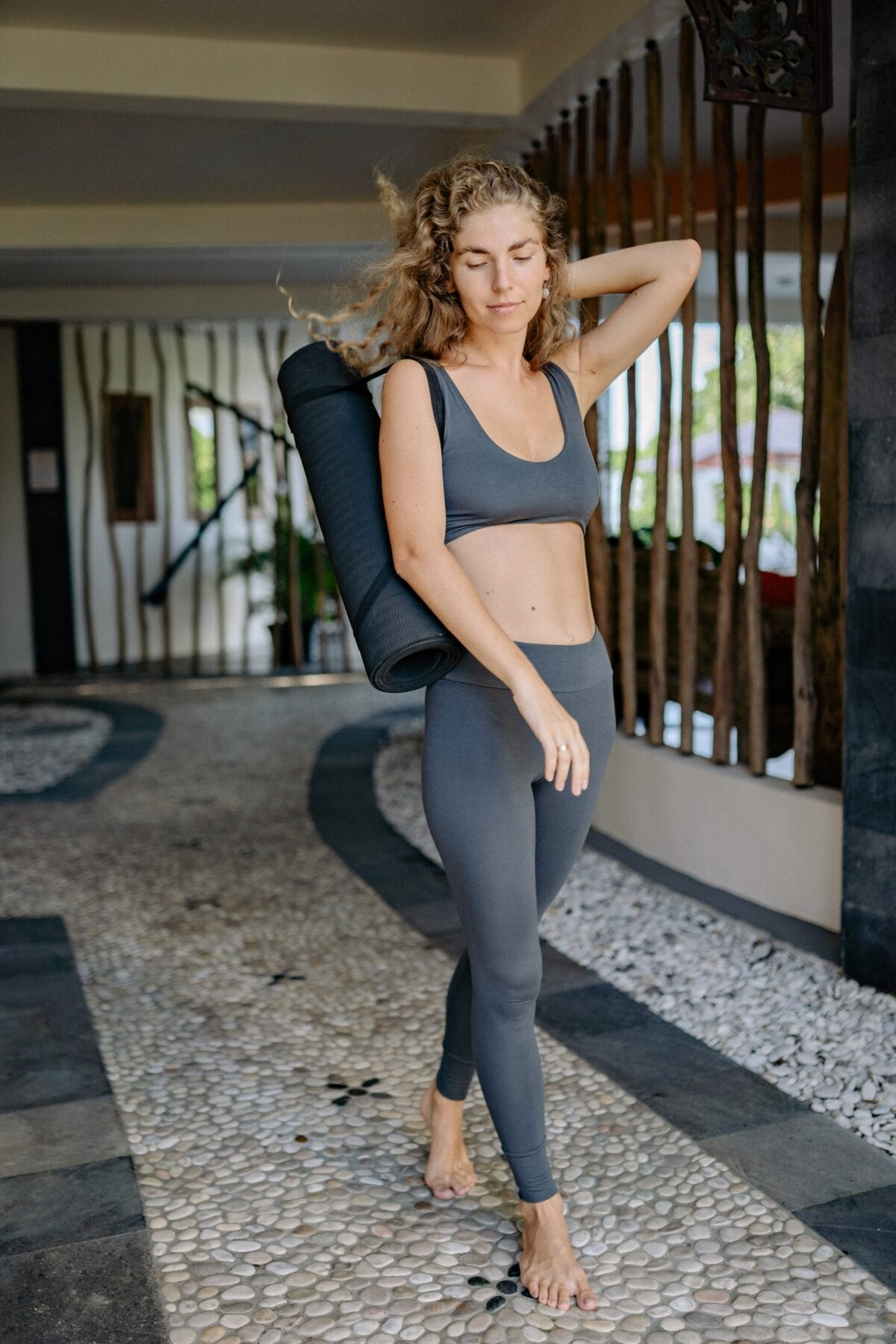 Sporty woman in sportswear with yoga mat on pathway